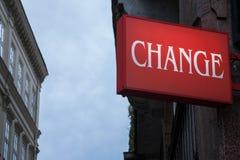 Signe rouge avec le changement de mot écrit, avec des bâtiments du fond, alors que la nuit s'approche Images stock