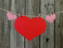 Signe rouge de coeur et coeurs rayés de tissu accrochant sur le clothlesline par le fond en bois minable Photographie stock libre de droits