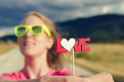 Signe se tenant femelle assez jeune des textes d'amour Fin vers le haut Photographie stock libre de droits