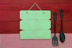 Signe vert vide accrochant par la nappe rouge de guingan sur le fond en bois Photographie stock libre de droits