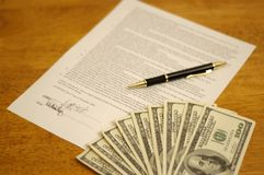 Signed contract. With pen, and money on top. Bills denomination $100 royalty free stock photos