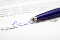Signed contract. Or document. Ballpoint pen resting on contract. Focus on the end of ballpoint pen. Shallow depth of field. Close-up Stock Photo