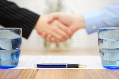 Signed contract with handshake in blur, focus on pen Stock Photo