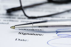 Signed document with pen and reading glasses. Stock Photo