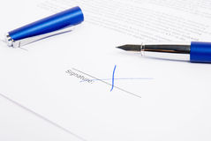 Signed Document With Pencil. Contract signed with blue X. Cap is still removed Royalty Free Stock Photo
