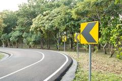 Signes avertissant le tour à gauche de la route de courbe Photographie stock libre de droits