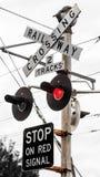 Signes de passage à niveau avec le signal de clignotant rouge Photo stock