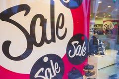 Signes de vente dans des fenêtres de boutique de magasin de chaussures Photos stock