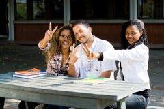 Signes de victoire d'étudiants universitaires images stock