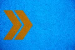 Signes jaune-orange de flèches dirigeant la bonne direction au-dessus du fond approximatif de mur de stuc bleu lumineux intense d images libres de droits