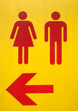 Signes jaunes à la toilette avec la flèche rouge Image libre de droits
