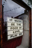 Signez au sujet de la musique et de l'amour dans une fenêtre de magasin avec la réflexion Photographie stock libre de droits