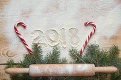 Signez la bonne année 2018 dans la farine sur la table en bois décorée des sucreries rouges, goupille en poudre par branche de No Photo libre de droits