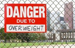 Signez le danger dû à accrocher de poids excessif sur la barrière image stock