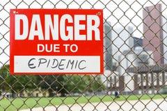 Signez le danger dû à l'épidémie accrochant sur la barrière photos libres de droits