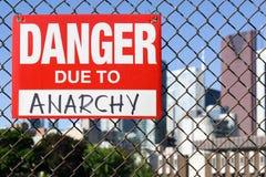Signez le danger dû à l'anarchie accrochant sur la barrière photos stock