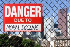 Signez le danger dû à la baisse morale accrochant sur la barrière image stock