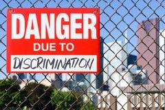 Signez le danger dû à la discrimination accrochant sur la barrière image libre de droits