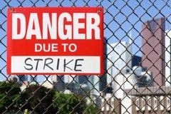 Signez le danger dû à la grève accrochant sur la barrière photographie stock