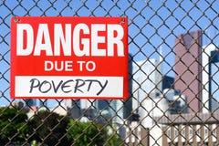 Signez le danger dû à la pauvreté accrochant sur la barrière image stock