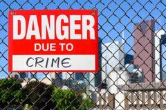 Signez le danger dû à la pendaison de crime sur la barrière photos stock