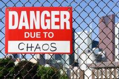 Signez le danger dû au chaos accrochant sur la barrière photographie stock libre de droits
