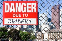 Signez le danger dû au corruption accrochant sur la barrière photos libres de droits