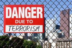 Signez le danger dû au terrorisme accrochant sur la barrière photo stock