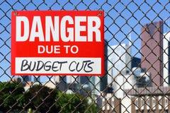 Signez le danger dû aux compressions budgétaires accrochant sur la barrière photographie stock libre de droits