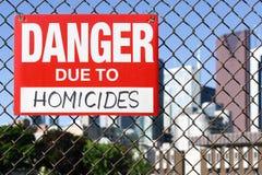 Signez le danger dû aux homicides accrochant sur la barrière photographie stock libre de droits