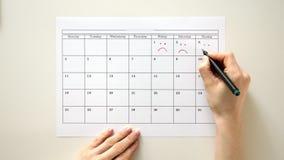 Signez le jour dans le calendrier avec un stylo, dessinez un sourire
