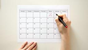 Signez le jour dans le calendrier avec un stylo, dessinez un sourire banque de vidéos