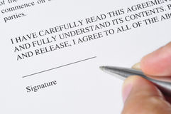 Signing. A hand, holding a pen, is ready to sign a document Royalty Free Stock Photography
