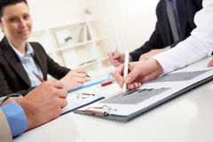 Signing agreement. Close-up of business person hand over document in working environment Stock Photos