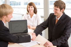 Signing of an agreement. Businessmen shake their hands against the background of a woman Royalty Free Stock Photo