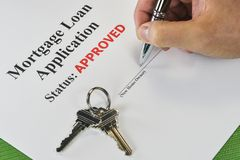 Signing An Approved Real Estate Mortgage Loan. Hand Signing An Approved Real Estate Mortgage Loan Document With House Keys royalty free stock images