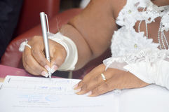 Signing of a bride. A bride is  putting her signature in the civil wedding register of the town hall Stock Image