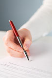 Signing a business agreement. A female person signing a business document - contract or an agreement Royalty Free Stock Images