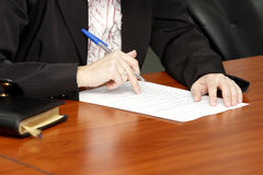 Signing a business contract. Photo of businesswoman's hands writing a business contract Royalty Free Stock Photos