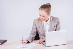 Signing a business contract. Woman Businessman sitting at the ta. Ble and typing a business plan on a laptop while businessman sitting at desk on isolated gray Stock Image