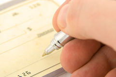 Signing check. Close up with shallow depth of field royalty free stock photos