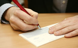 Signing of the check. The man's hand signs the check at office Royalty Free Stock Photo