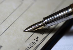 Signing the Check. Fountain pen on a check, ready to sign Stock Photos