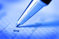 Signing a Check for Personal Finances. Pen on paper money financial stock photography
