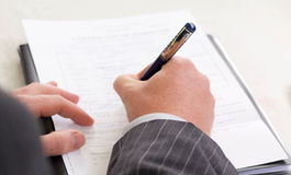 Signing contract. A corporate man signing a legal contract Royalty Free Stock Photos