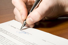 Signing Contract. Close up of the hand holding the pen and signing the contract Stock Images