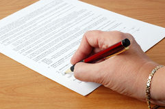 Signing A Contract. Close-up of a female hand signing a contract Stock Photography