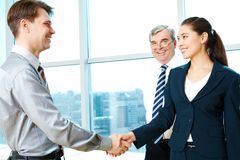Signing contract. Photo of successful partners handshaking after signing agreement Royalty Free Stock Images