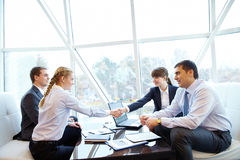 Signing contract. Photo of confident partners handshaking at meeting after making an agreement Stock Images