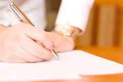 Signing contract. Macro shot of a business man signing a contract - end of the pen in focus Royalty Free Stock Image